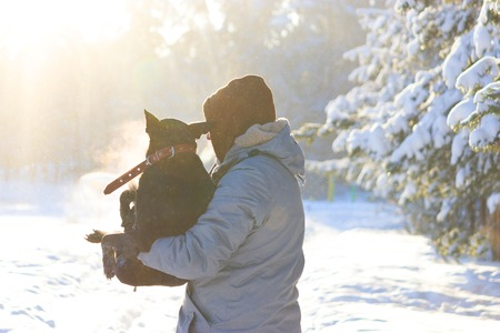 man take dog on his arm, because the dog is ill. winter Stock Photo