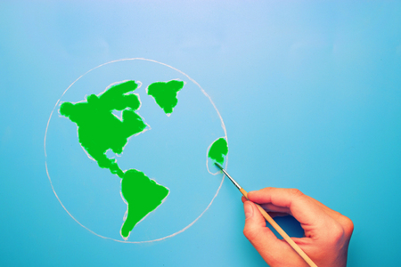 hand with brush painting world map in green color. go green concept