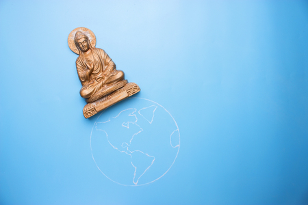 buddha statuette on the earth. peace in the world concept