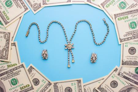 100 dollar bills and jewellery. invest money in jewellery concept