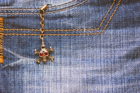 Skull brooch on torn jeans . close up. copy space
