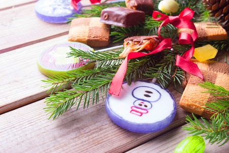 christmas sweets on wooden background. pine tree branches