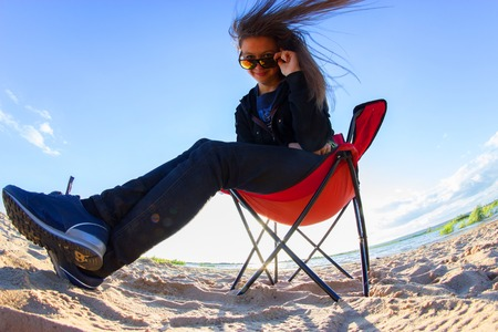 young arrogant woman sit on the beach chair