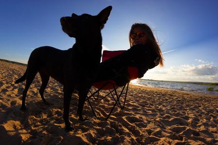 girl in beach chair with dog on the beach