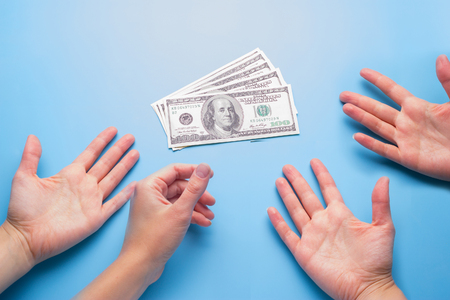 many hands reach for money. borrow money, greed concept