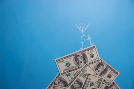 man standing on the dollars in a shape of a mountain. earn money concept