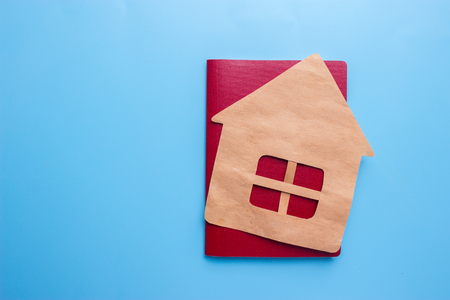 Passport and house on blue background. acquisition of nationality concept Stock Photo