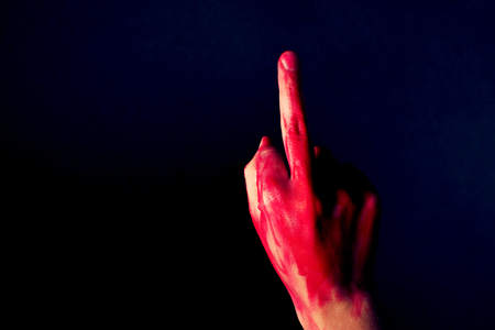 Hand with blood showing middle finger on black background