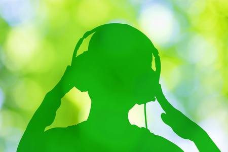 sihouette of a girl listening to relax music on nature background
