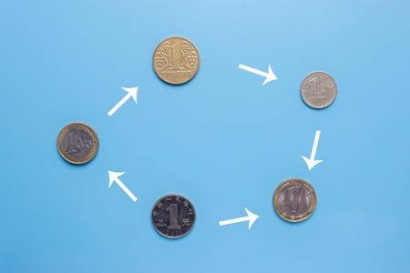 currency exchange concept. different coins on blue background Stock Photo