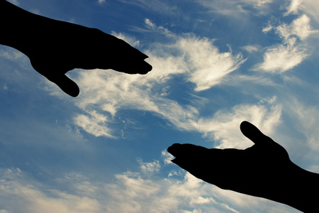 silhouette of helping hand on sky background