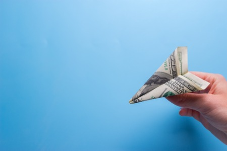 Flying paper plane with dollar banknote holding in hand