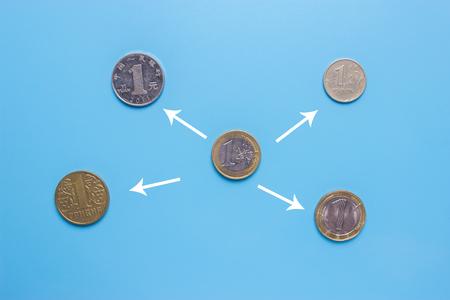concept d & # 39 ; échange de devises . différentes pièces sur fond bleu