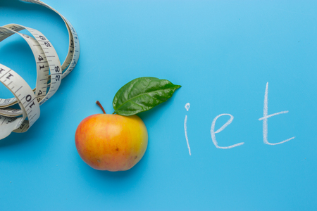 Apples with tape measure on blue background, lose weight concept
