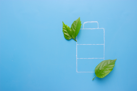 Eco green energy battery on blue background Stock Photo