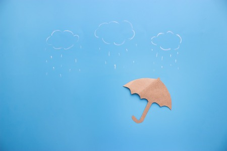 Painting of cloud and rain with umbrella on blue background