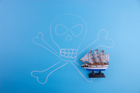 pirate ship with jolly rodger on blue background