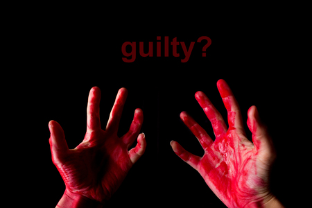 innocent or guilty concept. bloody hand on black background Stock Photo
