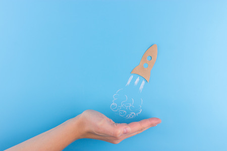 rocket made from paper on blue background. business concept