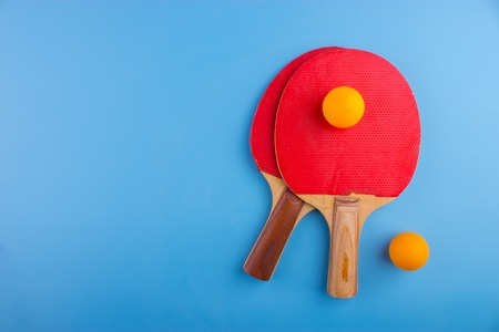 Table tennis rackets and balls on blue background