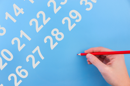 A female hand circling the date with red pen Stock Photo
