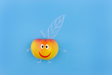 Funny fruit character Smiling Apple on blue background