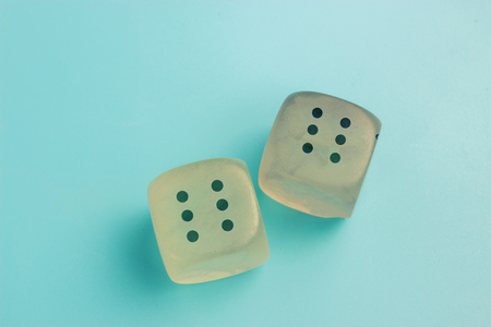 two loaded dice. six and six. blue background