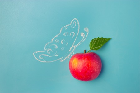 butterfly on the apple on blue background Stock Photo