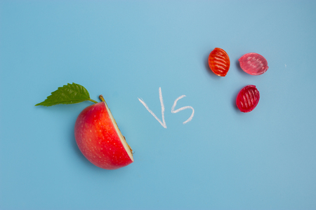 half of an apple and sweet food. unhealthy vs healthy food Stok Fotoğraf