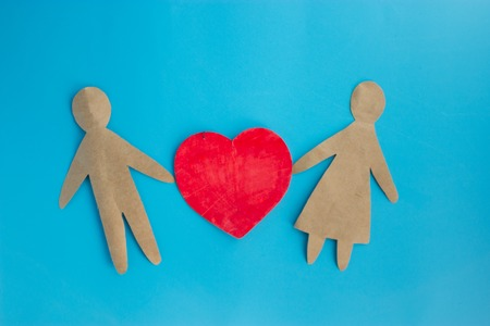 Paper people together in love on blue background