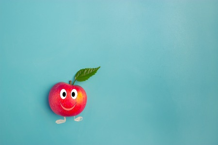 fresh red apple with green leaf on blue background