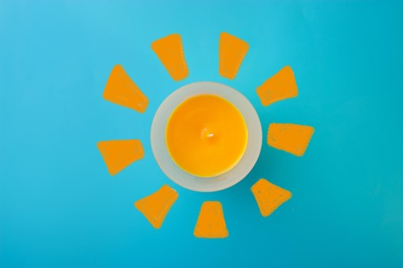 orange aroma candle with sun drawing on the blue background