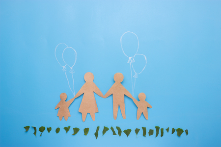 paper family on blue background and green grass