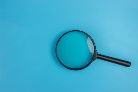 Magnifying Glass on blue background. copy space
