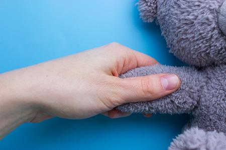 dziewczyna trzymając się za ręce misia na niebieskim tle