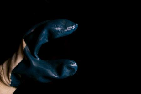 Une main tenant un symbole de radioactivité sur fond noir