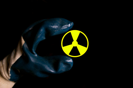 A hand holding a symbol for radioactivity on black background