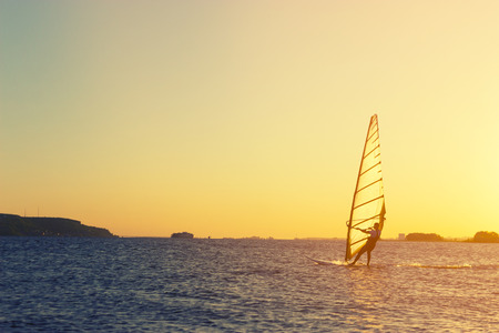 man on wind surf against sunset sky background