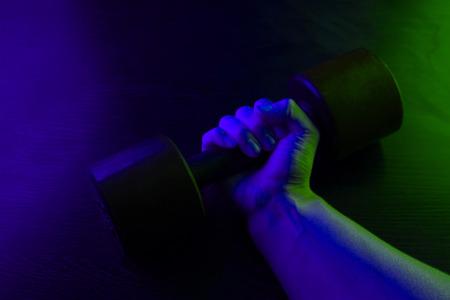 metal barbell on dark background in neon light