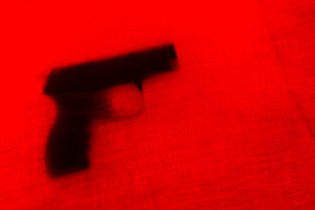 handgun behind red curtain. close up. soft focus Stock Photo