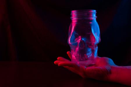 skull shaped glass in neon light. dark background