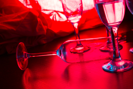 glass with alcohol in neon light in a bar or club