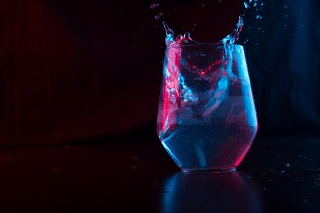 Water gemarkeerd in blauw en rood spatten in een glazen beker op een zwarte achtergrond Stockfoto