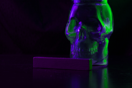 poison conceptual image. green skull on dark background