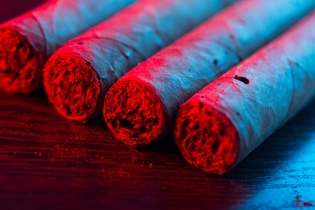 Close up of cigars in neon light
