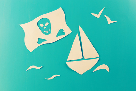 pirate ship concept image. paper cut on blue background