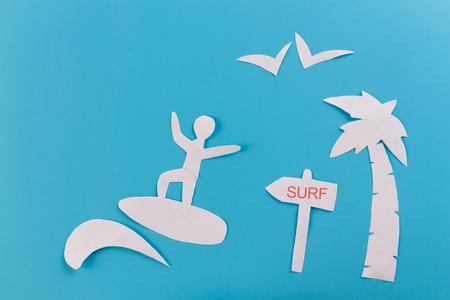 Surfer on wave. blue background. paper cut