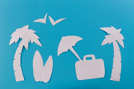 suitcase on the beach with palms. paper cut