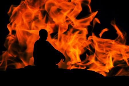 silhouette d'un moine, méditant sur fond de feu