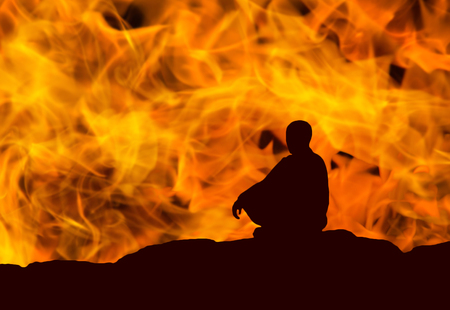 silhouette of a monk, meditating on fire background